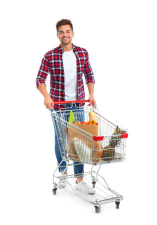 Young man with full shopping cart on white background Foto de archivo - 129914959