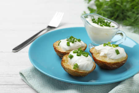 Delicious potato wedges with sour cream on white wooden table