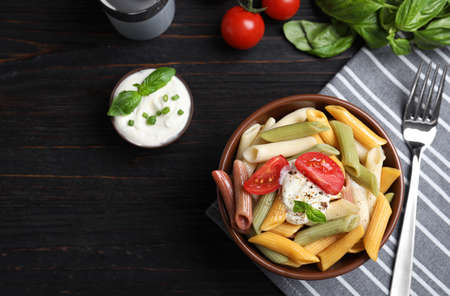 Delicious vegetable pasta with sour cream dressing on black wooden table, flat lay