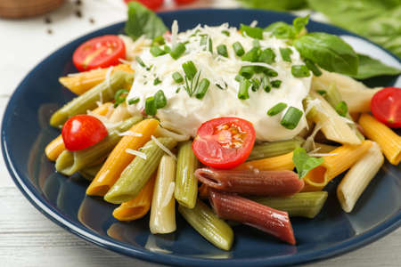 Delicious pasta with sour cream on white wooden table, closeup
