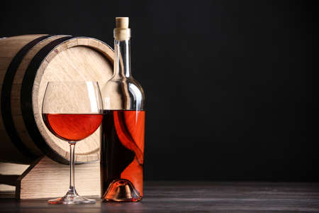 Wooden cask, bottle and glass of wine on table against dark background, space for text Stok Fotoğraf
