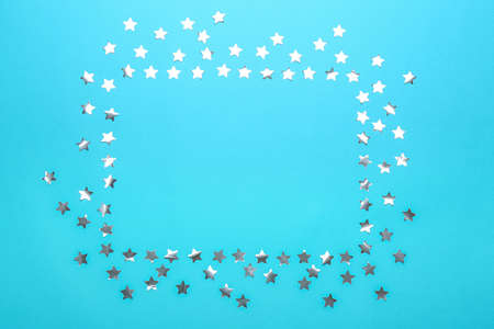 Frame made of confetti stars with space for text on blue background, top view. Christmas celebration