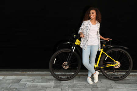 Beautiful young African-American woman with bicycle near glass building. Space for text