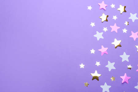 Confetti stars with space for text on violet background, top view. Christmas celebration