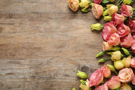 Flat lay composition with beautiful Eustoma flowers on wooden table, space for text 스톡 콘텐츠
