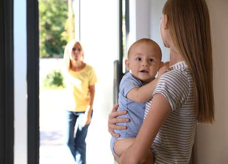 Madre dejando a su bebé con niñera adolescente en casa. Espacio para texto Foto de archivo