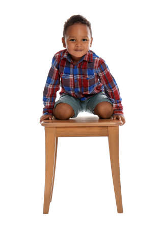 Little African-American boy climbing up stool on white background. Danger at home Stock Photo