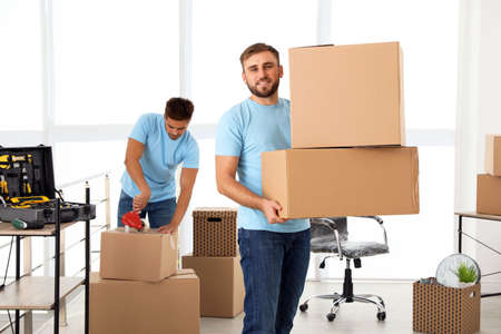 Young worker with cardboard boxes and his colleague in office. Moving service