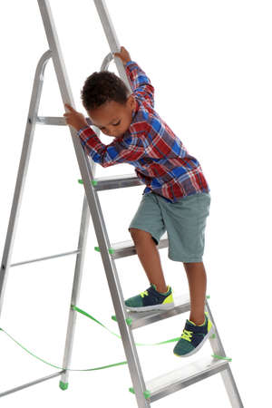 Little African-American boy climbing up ladder on white background. Danger at home Stock Photo