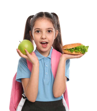 Surprised girl with burger and apple on white background. Healthy food for school lunch Stock Photo