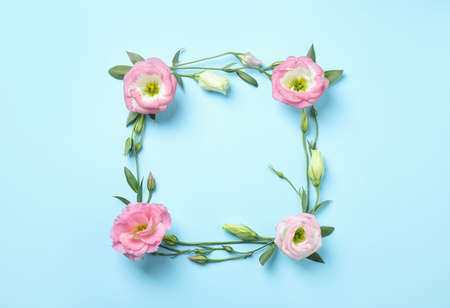 Flat lay composition with beautiful Eustoma flowers on light blue background, space for text