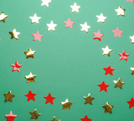 Frame made of confetti stars with space for text on green background, top view. Christmas celebration 스톡 콘텐츠