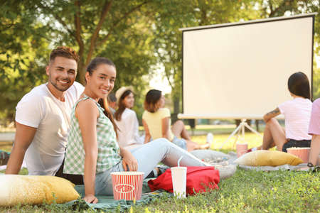 Young couple with popcorn watching movie in open air cinema. Space for text Stock fotó