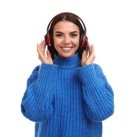 Mujer joven escuchando música con auriculares sobre fondo blanco.
