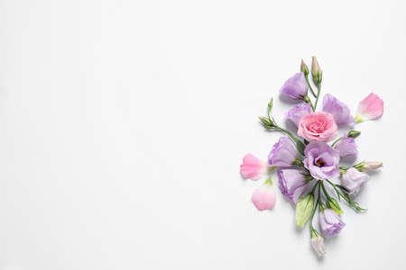 Beautiful Eustoma flowers on white background, top view. Space for text