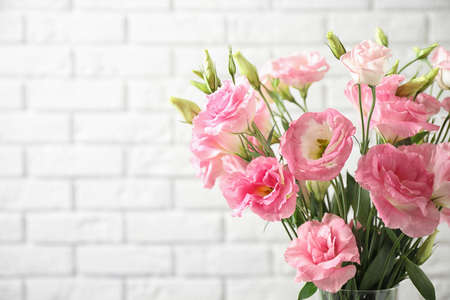 Eustoma flowers near white brick wall, space for text 스톡 콘텐츠