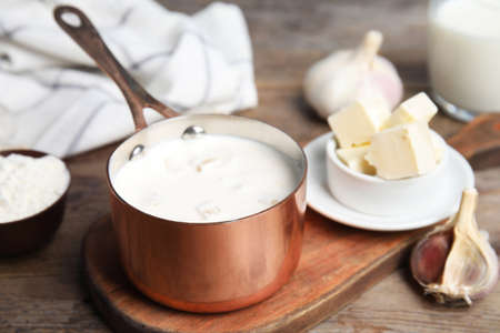 Delicious creamy sauce in pan on wooden table 스톡 콘텐츠