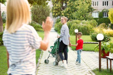 Madre dejando a los niños con niñera adolescente en el parque