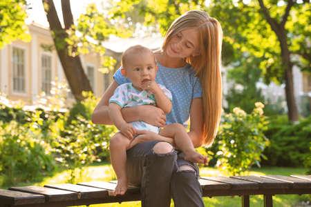 Niñera adolescente con lindo bebé al aire libre en un día soleado Foto de archivo