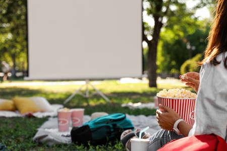 Donna con popcorn che guarda film nel cinema all'aperto, primo piano. Spazio per il testo