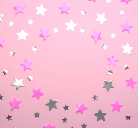 Frame made of confetti stars with space for text on pink background, top view. Christmas celebration