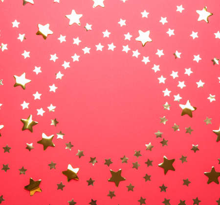 Frame made of confetti stars with space for text on red background, top view. Christmas celebration Imagens