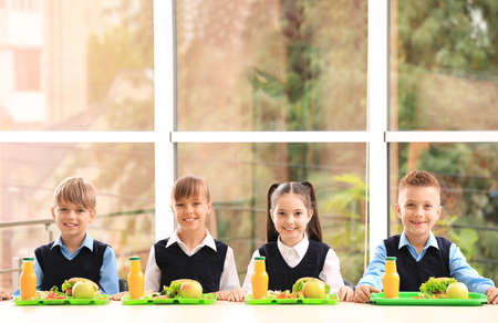 Happy children at table with healthy food in school canteen Stock Photo