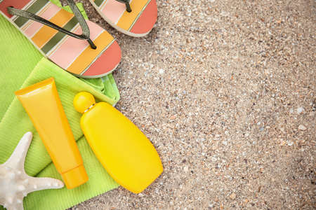 Flat lay composition with bottles of sun protection body cream on sand beach, space for text