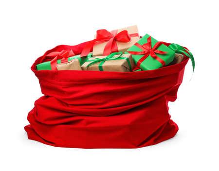 Bolsa roja de Santa Claus llena de regalos aislado en blanco Foto de archivo