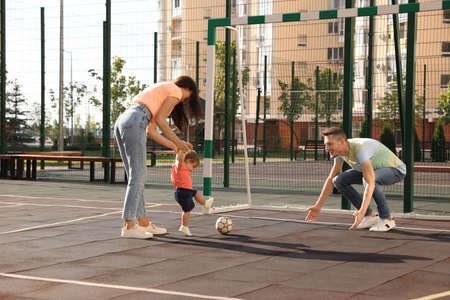 Happy family with adorable little baby playing football outdoors Stockfoto