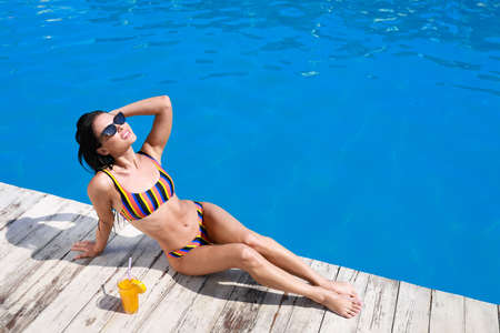 Beautiful young woman in bikini with refreshing cocktail near swimming pool on sunny day. Space for text