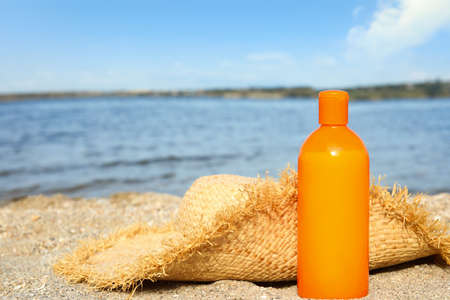 Bottle of sun protection body cream and hat on beach, space for design Reklamní fotografie - 129736075
