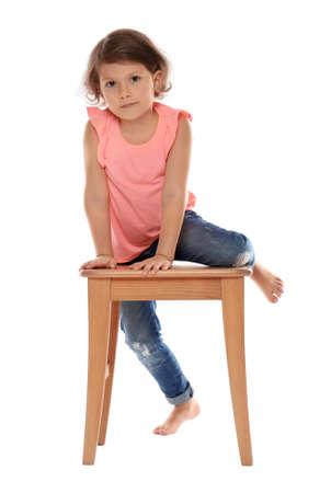 Little girl on stool against white background. Danger at home Foto de archivo