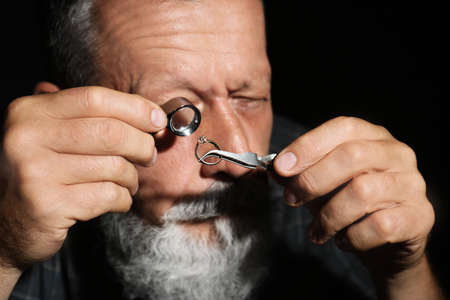 Male jeweler evaluating diamond ring in workshop, closeup view Stok Fotoğraf