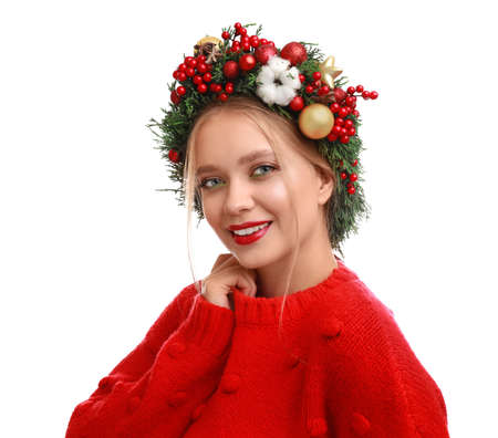 Beautiful young woman wearing Christmas wreath on white background