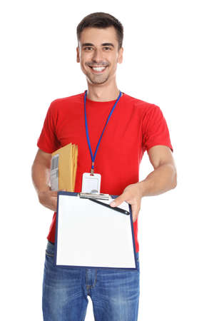 Happy young courier with clipboard and envelopes on white background Фото со стока