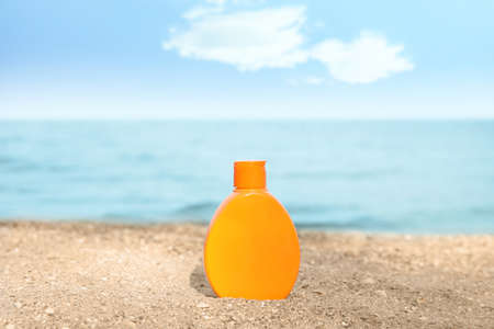 Bottle of sun protection body cream on beach, space for design