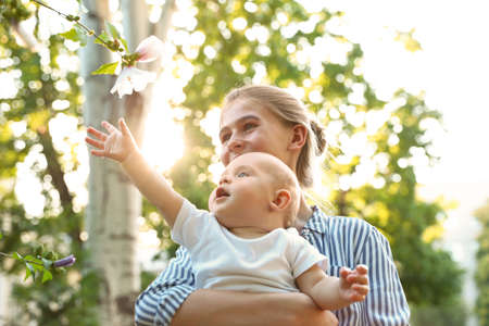 Teen nanny with cute baby in park on sunny day