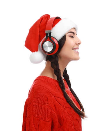 Young woman in Santa hat listening to Christmas music on white background Фото со стока - 129919186