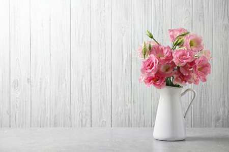 Eustoma flores en florero en la mesa junto a la pared blanca, espacio para texto