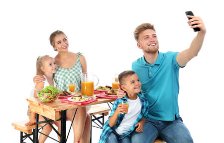 Happy family taking selfie at picnic table on white background Archivio Fotografico - 129919343