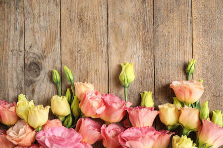 Flat lay composition with beautiful Eustoma flowers on wooden table, space for text