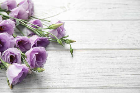 Beautiful fresh Eustoma flowers on white wooden table, space for text