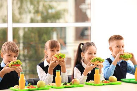 Happy children eating healthy food for lunch in school canteen 免版税图像