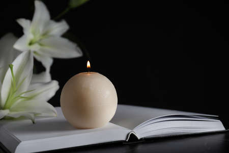 Burning candle, book and white lilies on table in darkness, closeup with space for text. Funeral symbol