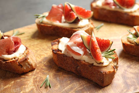 Bruschettas with cream cheese, prosciutto and figs served on wooden board, closeup