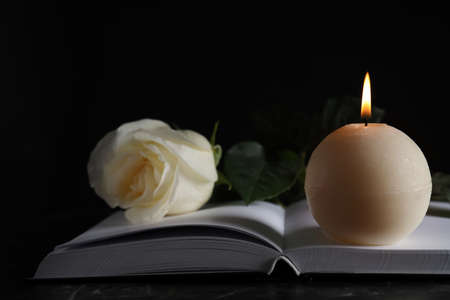 Burning candle, white rose and book on table in darkness, closeup. Funeral symbol