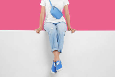 Woman wearing stylish shoes on color background, closeup