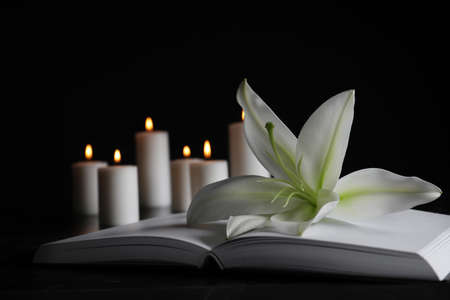 White lily, book and blurred burning candles on table in darkness, closeup with space for text. Funeral symbol