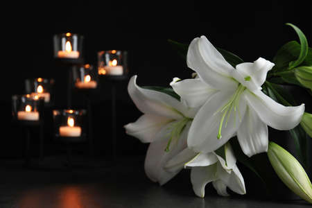White lilies and blurred burning candles on table in darkness, closeup with space for text. Funeral symbol